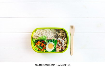 Healthy food concept: Lunch box filled with rice, mixed vegetables, boiled egg and nuts and fork on white wooden background with copy space; top view, flat lay