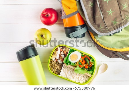 Healthy food concept: Lunch box filled with rice, mixed vegetables, boiled egg and nuts near thermos mugs and backpack on white wooden background; top view, flat lay