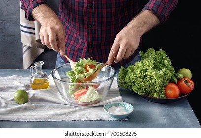 Healthy food concept. Man cooking salad In the home kitchen