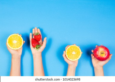 Healthy food concept. Many kids hands with fuits on blue background