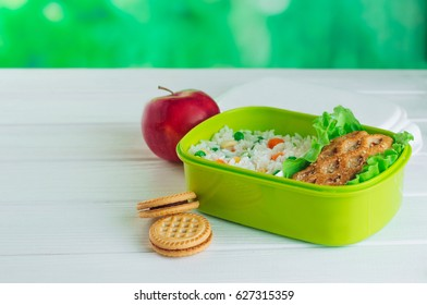 Healthy food concept: Open lunch box filled with rice and sandwich on white wooden background with copy space; selective focus