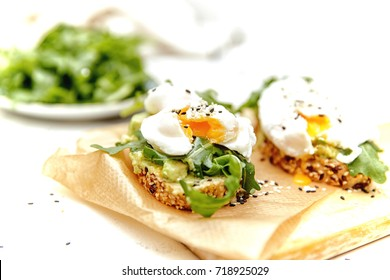 Healthy food concept - sandwich with arugula, avocado and poached egg.