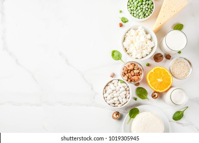 Healthy food concept. Set of food rich in calcium - dairy and vegan Ca products, white marble background top view copy space