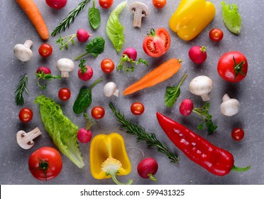 Healthy food concept. Studio photography of different vegetables and greenery on a grey background. Top view. Colorful food background.