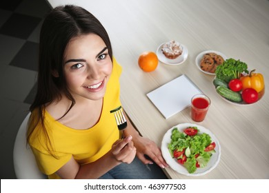 Healthy food concept. Young woman sitting at kitchen table