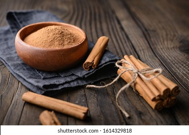 Healthy food condiment with medicinal properties, true Ceylon Cinnamon sticks and powder in a bowl on wooden background