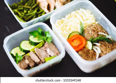 the healthy food in the containers on black background: snack, dinner, lunch. Baked fish, beans, beef cutlets, mashed potatoes, meat and vegetables tomatoes, cucumbers. top view