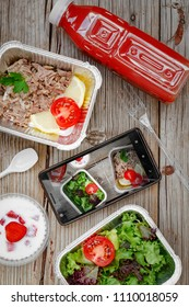 Healthy food delivery. Concept Proper nutrition, catering, business lunch. Smartphone and wholesome food in disposable containers on a wooden background. Take away of natural organic low carb diet. to