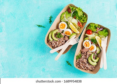 Healthy food delivery. Lunch- Buckwheat porridge, sliced tuna, boiled egg and fresh vegetable salad in zero waste containers  on blue background. Top view, flat lay