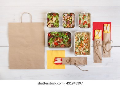 Healthy food delivery. Take away of natural organic low carb. Eat right concept, healthy food, fitness nutrition take away in aluminium boxes, cutlery and package, top view, flat lay at white wood