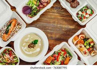 Healthy food delivery in white eco boxes. Fish, meat, soup and salads.