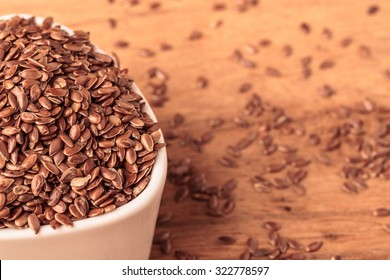 Healthy food diet. Brown flax seeds linseed in white bowl on wooden table