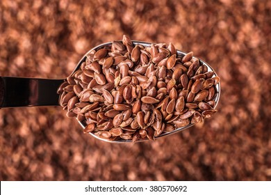 Healthy food diet. Closeup brown flax seeds linseed on kitchen spoon
