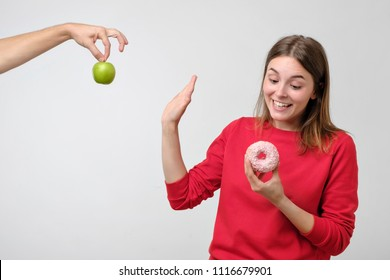 Healthy food and diet concept. Beautiful young woman choosing between fruits and sweets. She prefer a pink donut instead of green apple