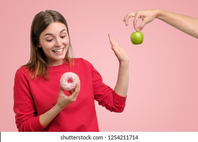 Healthy food and diet concept. Beautiful young woman in red clothes choosing between fruits and sweets standing on pink background. She prefer a delicious donut instead of green apple