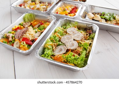 Healthy food and diet concept, restaurant dish delivery. Take away of fitness meal. Weight loss nutrition in foil boxes. Vegetable salad with rabbit meat at white wood