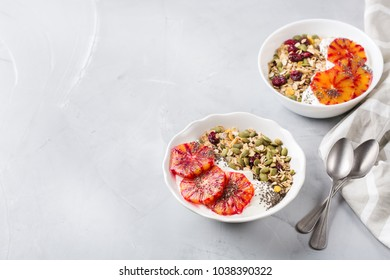 Healthy food, diet and nutrition concept. Early morning breakfast with homemade granola muesli, natural yogurt, seasonal ripe blood oranges. Copy space kitchen background