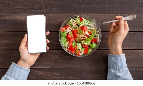 Healthy food and diet planning concept. Woman using smartphone with blank screen and eating fresh salad, top view