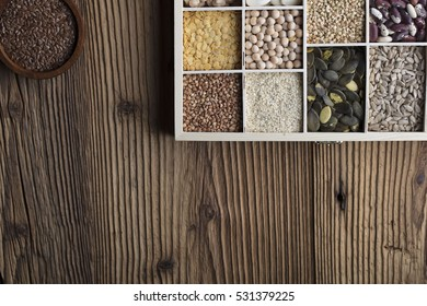 Healthy food and diet theme. Lentils, peas, beans, protein food in bowls, on a wooden table. Top view.