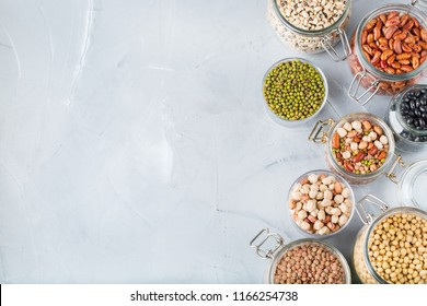 Healthy food, dieting, nutrition concept, vegan protein source. Assortment of colorful legumes in jars, lentils, soy kidney beans, chickpeas on a modern kitchen table. Top view flat lay background