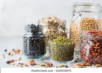 Healthy food, dieting, nutrition concept, vegan protein source. Assortment of colorful legumes in jars, lentils, soy kidney beans, chickpeas on a modern kitchen table