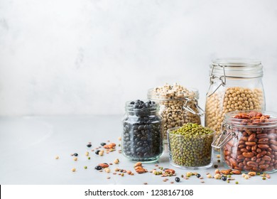 Healthy food, dieting, nutrition concept, vegan protein source. Assortment of colorful legumes in jars, lentils, soy kidney beans, chickpeas on a modern kitchen table. Copy space background