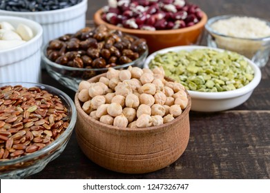 Healthy food, dieting, nutrition concept, vegan protein and carbohydrate source. Assortment of colorful raw legumes: red lentils, green peas, beans, chickpeas ; brown and white rice on a wooden table