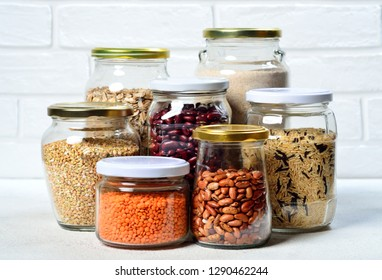 Healthy food, dieting, nutrition concept, vegan protein source. Assortment of colorful raw legumes and grain products in storage jars in pantry.