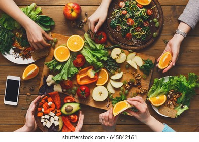 Healthy food dinner table. Women at home together, eating fruits and vegetables, top view, flat lay, crop