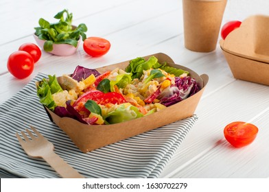 Healthy food in disposable eco friendly food packaging. Vegetable salad in the brown kraft paper food container on wooden background.