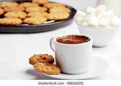 Healthy food & drink & natural diet food: Healthy breakfast. Coffee espresso milk, sugar & bakery. Coffee espresso, milk, sugar & cookie.  White linen tablecloths Closeup Focus on coffee crema