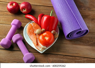 Healthy food, dumbbells and mat on wooden background
