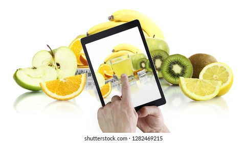 healthy food eating and balanced diet concept, hand pointing juice glass on digital tablet screen with fruits on background