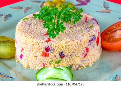 Healthy food eating: Couscous dish with raisins, peppers and salad on the side.