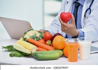 Healthy food eating nutritional concept with clean fruits with orange juice and milk and nutritionist holding red heart.