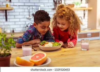Healthy food. Enigmatical boy leaning on table while going to have dinner
