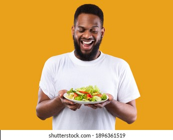 Healthy Food. Excited African Man Holding Vegetable Salad Plate Standing Over Yellow Studio Background. Male Dieting, Vegetarian Dinner Recipe And Weight Loss Concept