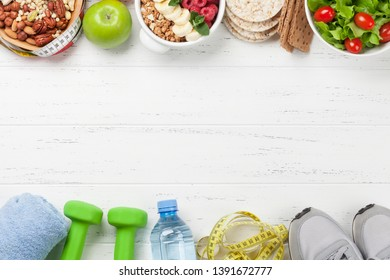 Healthy food and fitness concept. Various nuts, cereal, salad and dumbbels. Top view flat lay with copy space for your text