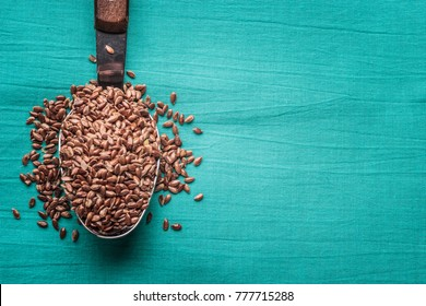 Healthy food. Flax seeds linseed on kitchen spoon linen green color background
