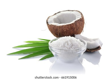 Healthy food. Fresh coconut with flakes in glass plate and green palm leaves isolated on white background