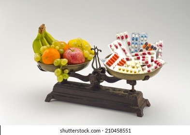 Healthy food. Fresh fruits and vegetables versus medical pills on a scale. White background.