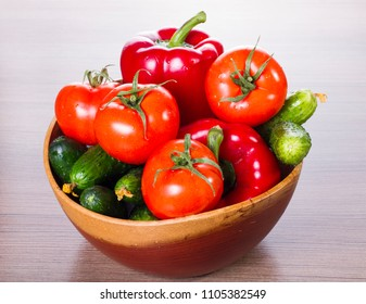 healthy food fresh vegetables. on a table in wooden plate cucumbers, tomatoes and pepper. Ingredients for Dietary Salad