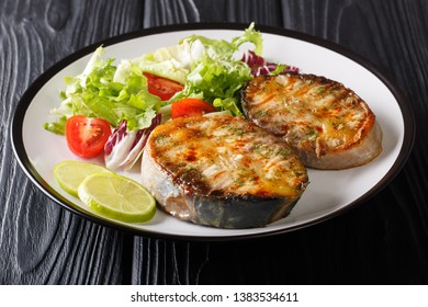 Healthy food fried sturgeon steaks served with fresh vegetable salad close-up on a plate on the table. horizontal