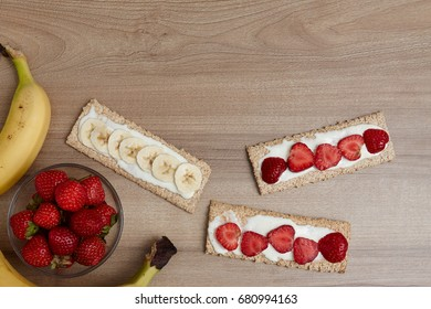 Healthy food. Fruit cut into bread and biscuits. A delicious dessert. Strawberry. Bananas. Fruits on a wooden background.