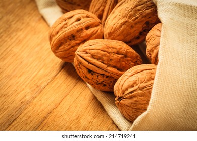 Healthy food full of omega-3 fatty acids, organic nutrition. Whole walnuts on rustic old wooden table