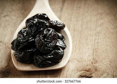 Healthy food, good cuisine. Closeup dried plums prunes fruits on wooden spoon rustic table background