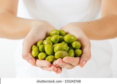 Healthy food green olive in human hands.