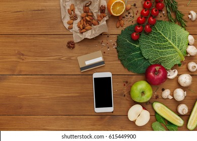 Healthy food, grocery online shopping with credit card. Fresh organic vegetables and fruits on wood table, top view, flat lay