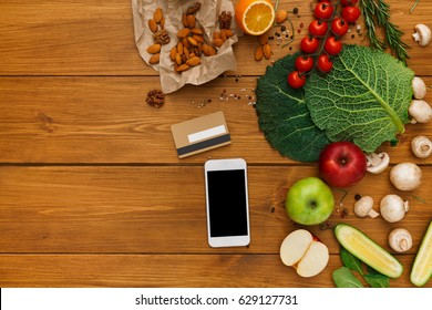 Healthy food, grocery online shopping, copy space on mobile screen. Fresh organic vegetables and fruits on wood table, top view, flat lay