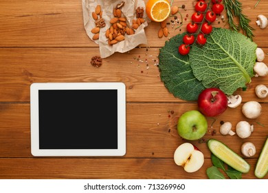 Healthy food, grocery online shopping, copy space on tablet screen. Fresh organic vegetables and fruits on wood table, top view, flat lay